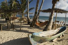 Corn Islands, Nicaragua. Traditional canoe, palm trees and thatched roof shacks on beach at Miss Elsa's.