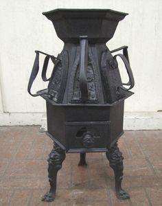 19th Century iron stove to heat 6 irons for tailor or laundry shop use. Protruding lip around the stove holds the flat bottom irons in plac...