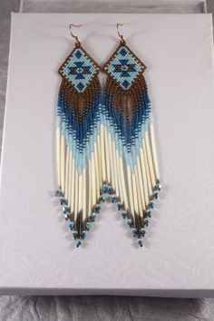 Hand-beaded with the smallest beads available, these unique earrings are done in dark copper, light blue/aqua and deep teal blue colors. The fringe includes authentic porcupine quill in their natural color and aurora borealis turquoise bicone Swarovski crystals for the perfect, eye-catching sparkle. These earrings are 5 7/8 in length, including the antique copper ear-wires, and an inch wide. I used brick (also called a Cheyenne) stitch to create them. They are ready to ship - rush s...