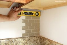 """Cute & cheap! 4 hours makeover using """"Cut, peal and stick"""" smart tiles for a kitchen backsplash. Start from the inside corner, using a utility knife and level."""