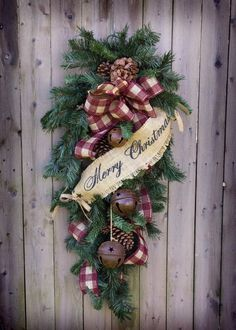"Our Christmas teardrop is 40"" long, and decorated with rusty bells and pine cones. Available with burlap ""Merry Christmas"" banner and burgundy check ribbon, or black and red check ribbon. Both picture"