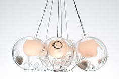 Vancouver-based Omer Arbel has produced numerous lighting fixtures and installations. among their designs is the '28.0 series light fixtures' made using a special glass blowing technique, where air is repeatedly blown in and then sucked out of heated and then cooled glass. the result of this process are distorted spheres with small LED lights placed inside. the '14.0 series pendant lamp' is a similar design made using cast glass spheres with frosted cylindrical voids.  #colorevolution