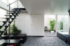 1階の砂利空間から奥の庭を見る。正面は寝室。左の階段は外部階段のように感じさせるために鉄骨に。また、階段部分で視線をブロックしないようにできるだけ薄くした。左の靴箱は、ベンチやパーティ時のテーブルとしても使用される。
