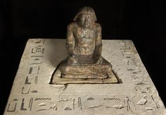 """Scribe statuette of Setka, son of Djedefre. Egypt, 4th Dynasty. Polished granite, 30 cm x 23 cm x 17 cm. The podest of the statue is made of polished limestone, its surface is engraved with Setka's name and titles. """"Eldest King's Son of His Body; Unique Servant of the King"""". Found in his father pyramid complex in Abu Rawash in 1901 by French archeologist Émile Chassinat."""