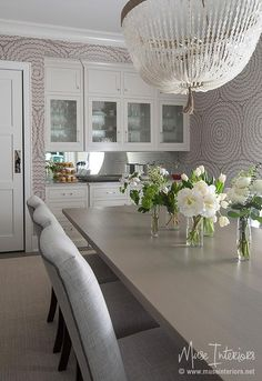 Gray dining room features a clear beaded chandelier, Ro Sham Beaux Malibu Chandelier, illuminating a gray wash wood dining table lined with heather gray linen dining chairs placed before a built-in bar fitted with seeded glass doors and a mirrored backsplash.