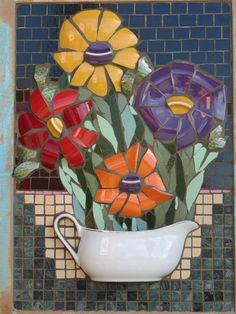 Quadro com flores de plástico e mosaico.