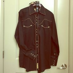 Black Men's Cowboy/Farmer black w/nude trim Shirt! Bought at Cavenders for my husband as a gift to wear to the rodeo. Wasn't his taste. Brand new with tags. Size Medium. Black with nude trim. Snap closure buttons...his loss is your gain. Price always negotiable! Belt featured not included but can be. Larry Mahan Cowboy Collection Tops