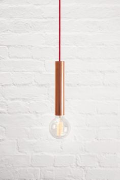 Modest and simple pendant lamp with single light. Here shown in charming combination of rose gold copper and red braided cord, with vintage Edison light globe.