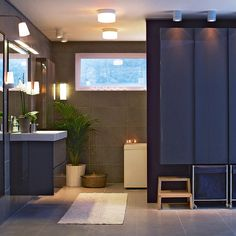 Godmorgon lighting over mirror  Sink cabinet and plant. Large grey square tile flooring.