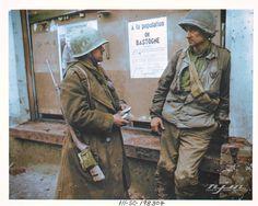 Pte Adam H. Davis (33794901) Philadelphia, Penns., & T5 Milford Abijha 'Bige' Sellars (35096829) Mooresville, Ind., of 110th Infantry Regiment, 28th US Infantry Division take a break before the eight-day German siege; Bastogne, Belgium - December 19, 1944