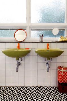 floor, sinks beneath windows, trashcan.... green orange, black and white. mmmm