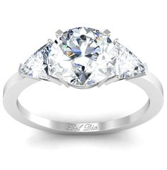 Three stone engagement ring with round brilliant center and trillion side diamonds.