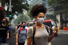Pedestrians are seen wearing masks as smoke haze from bushfires in NSW blankets the CBD in...