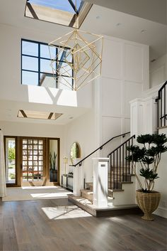 Farrow and Ball All White Foyer Two story foyer with skylight and grid board and batten wall Farrow and Ball All White Farrow and Ball All White #FarrowandBallAllWhite #foyer #gridboardandbatten #paintcolor