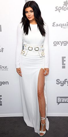 KYLIE JENNER in a form-fitting white dress with a belted waist and a mile-high slit, which she accessorized with T-strap sandals, at the 2015 NBCUniversal Upfronts in N.Y.C.