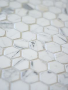 carrera hex tile. White subway tile to mid wall and top accent line with Carrera hex tile topped with white bull-nose.