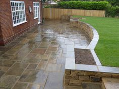 Back garden and patio in Dulwich with reclaimed Yorkstone paving, retaining wall and lawn.