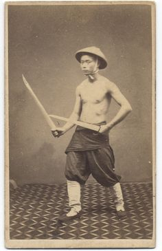 1860s photograph of a Chinese Soldier with butterfly swords. Subject unknown, taken by G. Harrison Grey.