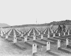 Description of  April 1945: White markers designate the final resting place for hundreds of Third and Fourth Marine Division fighters, who died during the invasion of Iwo Jima in World War II, in this cemetery located near the beach where the U.S. Marines first established a beachhead. In the background, an American flag flies at half staff in tribute to the late President Franklin D. Roosevelt, who died in Warm Springs, Ga., on April 12. (AP Photo/Murray Befeler)