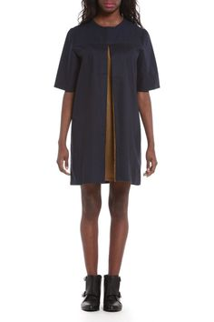 Midi-length navy dress with a green khaki exaggerated front pleat. Features oversized sleeves and cutout with a simple looped button closure at the center of back.