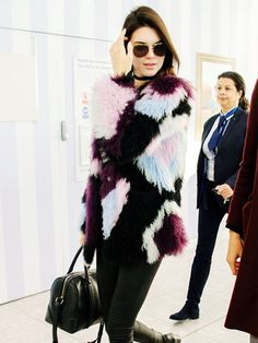 Kendall Jenner wears a patchwork fur coat with leggings, knee-high boots, a satchel, and aviator sunglasses