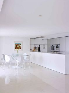 Minimalist white kitchen with Italian round glass dining table and white dining chairs - Kitchen Design | bulthaup Exeter | Sapphire Spaces - bulthaup b3 kitchen.