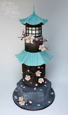 Pagoda cake with a blue roof against a very dark grey background. Touches of pink and a window with a white shade round it out.