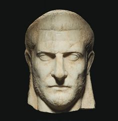 A ROMAN MARBLE PORTRAIT HEAD OF A MAN   CIRCA 2ND CENTURY A.D.   Lifesized, his closely-cropped hair summarily detailed, full on the sides above his pronounced ears, his heavy brow furrowed over convex unarticulated eyes, with thick lids, a strong aquiline nose, lightly-etched naso-labial folds, thin pursed lips, and a pronounced chin, his beard and mustache neatly groomed, the neck with projecting flanges on either side