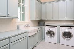 Simple modern laundry room with penny tiles, farmhouse sink and milk glass knobs.
