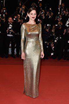 Red carpet em Cannes com o look das famosas. Marion Cotillard com lindo vestido dourado de manga comprida, cabelo preto e batom ruivo.