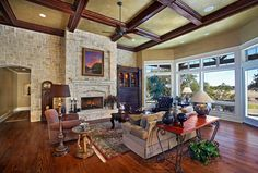 Dark wood ceiling beams and floors with large windows adds drama to this #livingroom