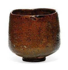 A Raku Chawan, (18th century) The irregular-shaped deep chawan in an ochre glaze with spatula marks, impressed seal Ohi, 9.5cm. high