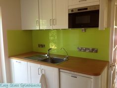 Gorgeous Lime Green coloured glass splashback in a White Kitchen with Wooden Worktops. Visit easyglasssplashbacks.co.uk to discover more.