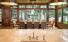 Brightly lit dining room wrapped in floor to ceiling windows holds a commanding view of the outdoors. Looking over the marble topped island, we see a lengthy natural wood dining table with fabric wrapped wood chairs, beneath a cage style chandelier.