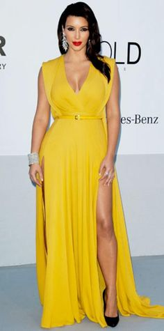 MAY 27, 2012 Kim Kardashian WHAT SHE WORE Kardashian arrived for the amfAR gala in a belted yellow gown. She finished the look with diamond jewelry and patent leather pumps.