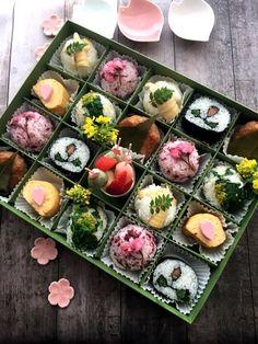 仕切りのある箱にさくら風味のつくねと卵焼き花びら型魚肉ソーセージ 竹の子 菜の花のおにぎり お花の太巻き 三色団子のスイーツを詰めたお花見弁当です。