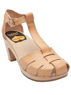 Duck toe sandal in tan from Swedish Hasbeens. These leather T-strap sandals feature a round toe with cut-outs, closed heel with adjustable buckle ankle strap, and contrast metal stitching on wooden clog platform. Platform measures .5