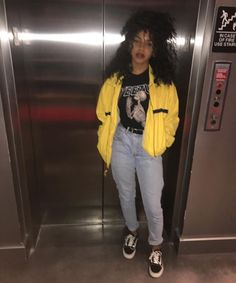Big curly hair + yellow jacket + black graphic shirt + mom jeans + black sneakers