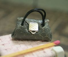 Handmade miniature handbag. Textured grey leather with a silver trim.