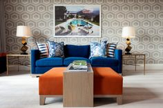 blaues sofa oranger hocker heller teppichboden geometrische tapeten