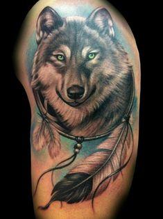 tatuaj geométrico, tatuaje grande en el brazo para hombres, motivos indianos, cabeza de lobo con ojos verdes, plumas