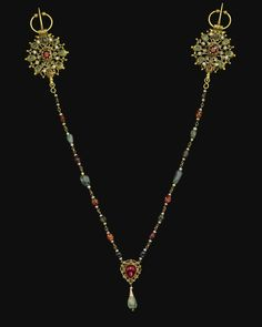 A PEARL AND GEM-SET GOLD FIBULAE (KHALLALAT), MOROCCO, 18TH CENTURY consisting of a long golden chain with polychrome gemstones and pearls, featuring a drop shaped red gemstone and hanging emerald in centre, both ends with an openwork roundel designed with scrolls and set with a red gemstone to the centre and green, blue and pearls around it, both with a hook and stud