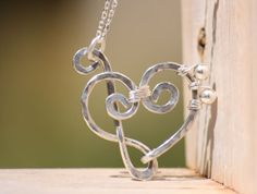 STERLING Silver Treble Clef and Bass Clef HEART Pendant Necklace     A treble and bass clef come together to create a heart in the middle, thus, this is the perfect gift for anyone who has a love for music!     The pendant measures approximately 1.25 inches tall and 1.25 inches wide. The whole necklace is made from sterling silver. The hammered silver creates so much reflection of light and it is truly beautiful.