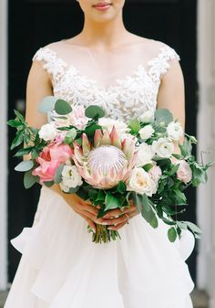 Bouquet by Blush and Bloom in Toronto, Ontario. From the florist: This bride requested a garden style bouquet in light, soft tones, but with a pop of coral and a unique twist with the focal flowers of her wedding, which were coral peonies and protea. Flowers: Coral peonies, blush dahlias, king protea, blush garden roses, white lisianthus, white ranunculus. Photography by Tara McMullen .