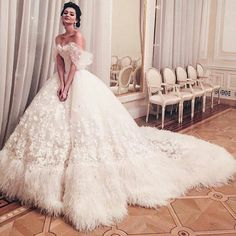 "Ivory tulle wedding ball gown heavily embellished with appliqued flowers and about 20"" border of ostrich feathers around the hem, including the train. I just wish I knew who made this. Kudos to the designer."