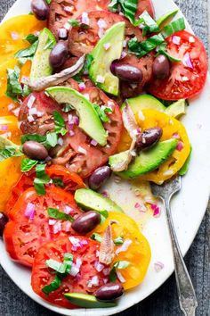 Here is 10-minute recipe for a simple tomato salad with anchovies, basil, olives and avocado. It's a healthy and simple side-dish to share with friends and family or to bring to a picnic or barbecue. It is paleo and dairy-free and ready in only 10 minutes! Healthy Seasonal Recipes by Katie Webster | #tomato #salad #summer #paleo #dairyfree #healthy #sidedish #lowcarb