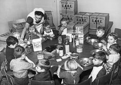 Around the table: A Dutch nurse feeds children orphaned with the contents of the aid packages sent to Europe from America