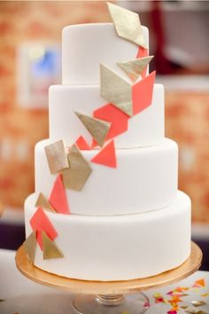 .modern collection: clean, white wedding cake with gold and coral-orange geometric detail