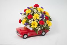 Teleflora's Ford Mustang Bouquet Celebrate his special day with a true classic! This ceramic model of the Ford Mustang holds an all around arrangement with red mini carnations, yellow daisy poms, purple statice and babies breath. x Item# 1194 Mini Carnations, Babies Breath, Ford Mustang, Special Day, Fathers Day, Daisy, Bouquet, Yellow, Purple