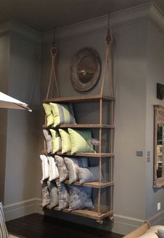 With some manila, wood planks, and a pair of rope thimbles (or pulleys) you can easily build your own version of these in-store display shelves from Restoration Hardware.
